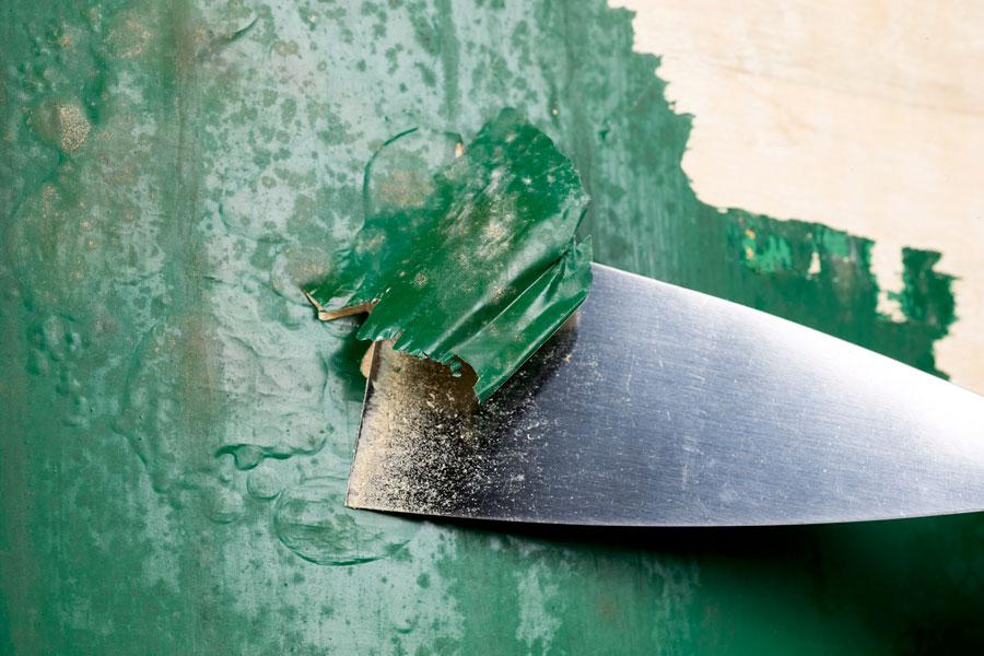 Detalle del decapante retirado con espátula en la restauración de un mueble.